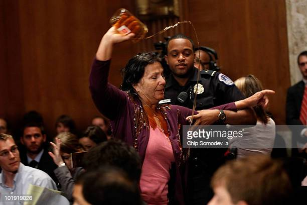 Commercial fisherwoman Diane Wilson of Seadrift Texas pours a jar of syrup made to look like oil over herself as a US Capitol Police officer drags...