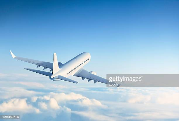commercial jet flying over clouds - aircraft stock photos and pictures