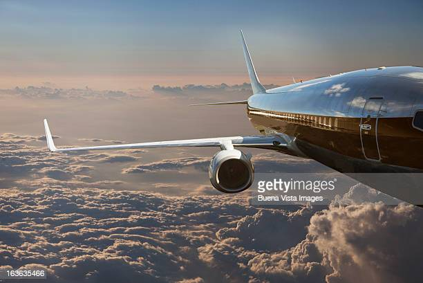 commercial jet flying over clouds - jet engine stock photos and pictures