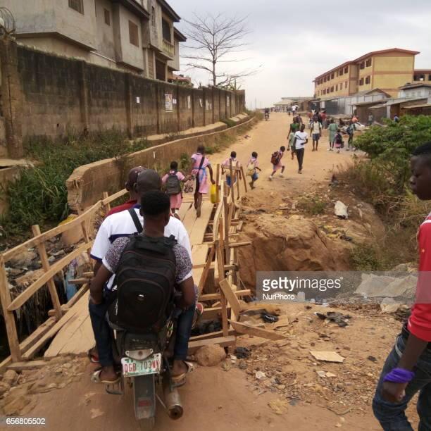 Commercial motorcyclist and school children crossing make-shift bridge at Egunjobi area of Aboru, Lagos Nigeria on Monday, March 21 2017. PHOTO:...
