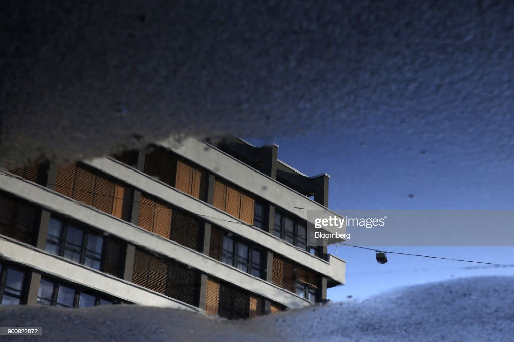 A commercial office building is reflected in a puddle of water in Bern, Switzerland, on Monday, Jan. 1, 2018. The supply of uninhabited apartments for rent has increased faster than the Swiss population has grown. Photographer: Stefan Wermuth/Bloomberg via Getty Images