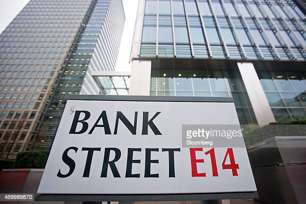 Commercial office buildings stand beyond aBank Street road sign in the Canary Wharf business, financial and shopping district of London, U.K., on...