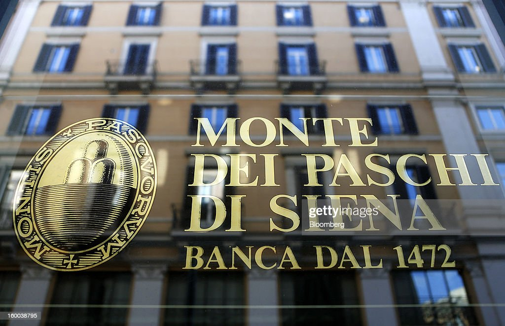 Commercial offices are reflected in the window of a Banca Monte dei Paschi di Siena SpA bank branch in Rome, Italy, on Friday, Jan. 25, 2013. Italian Prime Minister Mario Monti said the Bank of Italy will take another look at Banca Monte dei Paschi di Siena SpA's books after the company disclosed this week it may face more than 700 million euros of losses related to structured finance transactions hidden from regulators. Photographer: Alessia Pierdomenico/Bloomberg via Getty Images