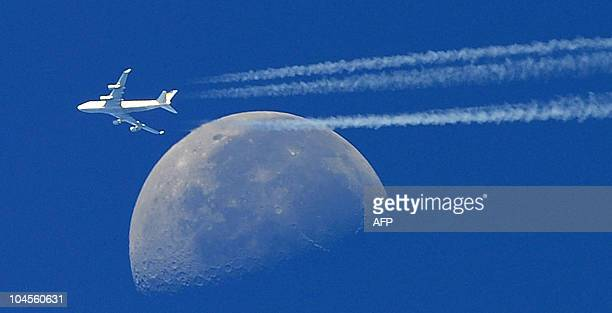A commercial plane a Boeing 747 flying in front of the moon on September 30 2010 is seen from Martigues close to Marseille southern France 30...