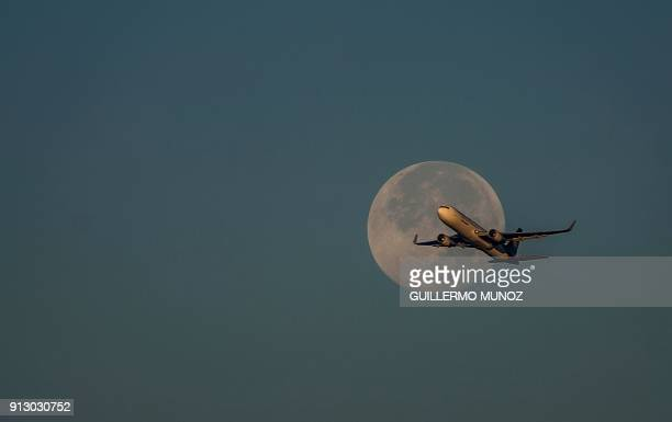 A commercial plane flies over Bogota as a 'super blue moon' is seen on February 1 2018 Skywatchers witnessed a rare lunar eclipse that combines three...