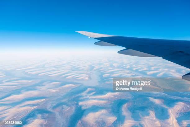 commercial plane flying over the arctic at sunset - inquadratura da un aereo foto e immagini stock