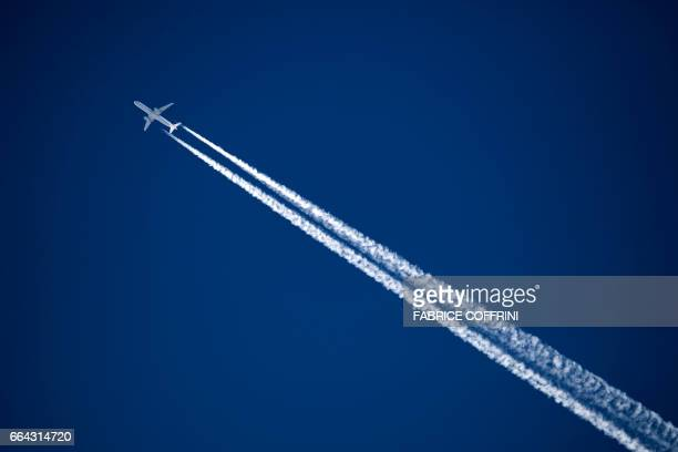 TOPSHOT A commercial plane of German airline Lufthansa leaves a contrail on the sky on April 3 2017 above the Swiss Alps resort of Verbier / AFP...