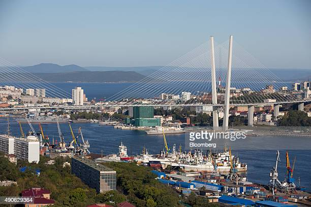Commercial shipping vessels sit at moorings on the waterway beneath Golden bridge in Vladivostok Russia on Monday Sept 28 2015 'It is simply...
