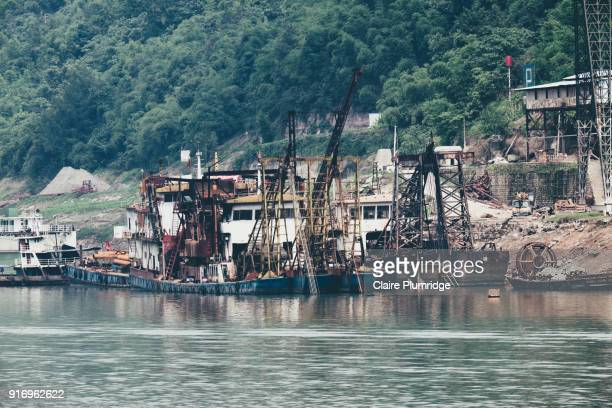 commercial ships with cranes on, docked on the shore of the yangtze river, china. - claire plumridge stock pictures, royalty-free photos & images