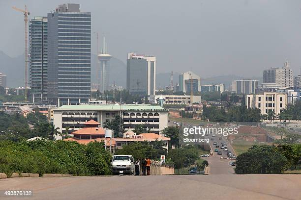 Commercial towers sit on the city skyline beyond a highway in Abuja Nigeria on Wednesday Oct 21 2015 A drop in crude prices in the past year has put...