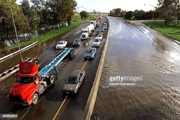 Commercial trucks and cars make their way through the flooded north and southbound lanes of 710 Long Beach Freeway the main artery to Long Beach and...