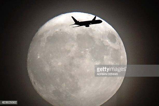 A commerical jet flies in front of the moon on its approach to Heathrow airport in west London on November 13 2016 Tomorrow the moon will orbit...