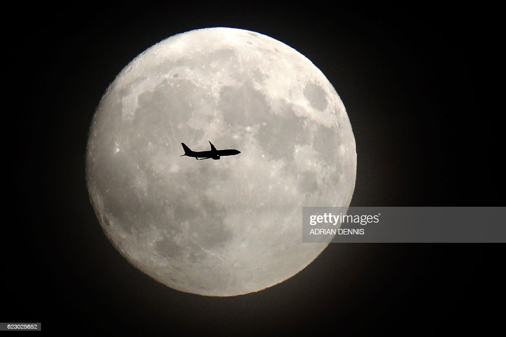 TOPSHOT - A commerical jet flies in front of the moon on its approach to Heathrow airport in west London on November 13, 2016. Tomorrow, the moon will orbit closer to the earth than at any time since 1948, named a 'supermoon', it is defined by a Full or New moon coinciding with the moon's closest approach to the Earth. / AFP / Adrian DENNIS