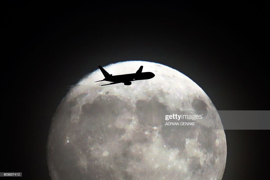 A commerical jet flies in front of the moon on its approach to Heathrow airport in west London on November 13, 2016. Tomorrow, the moon will orbit closer to the earth than at any time since 1948, named a 'supermoon', it is defined by a Full or New moon coinciding with the moon's closest approach to the Earth. / AFP / Adrian DENNIS
