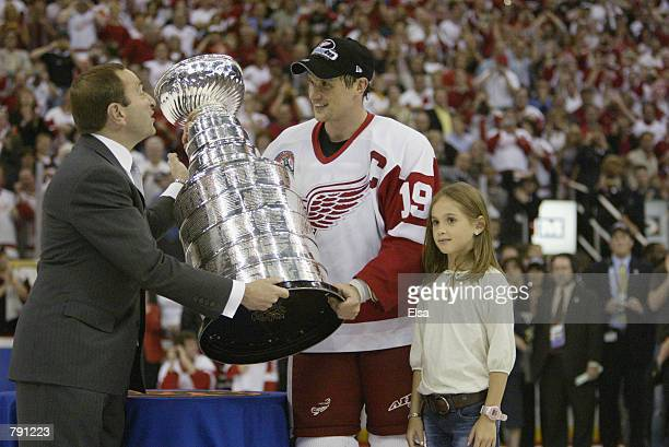Commisioner Gary Bettman presents the Stanley Cup to captain Steve Yzerman of the Detroit Red Wings with his daughter Isabella after eliminating the...