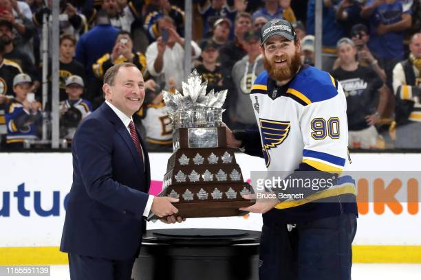 NHL commisoner Gary Bettman presents Ryan O'Reilly of the St Louis Blues with the Conn Smythe Trophy after defeating the Boston Bruins 41 to win Game...