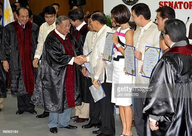 Commission on Elections Chairman Jose Melo shakes hands with the newly elected Philippine senators elected senators Ramon 'Bong' Revilla Jnr Jose...