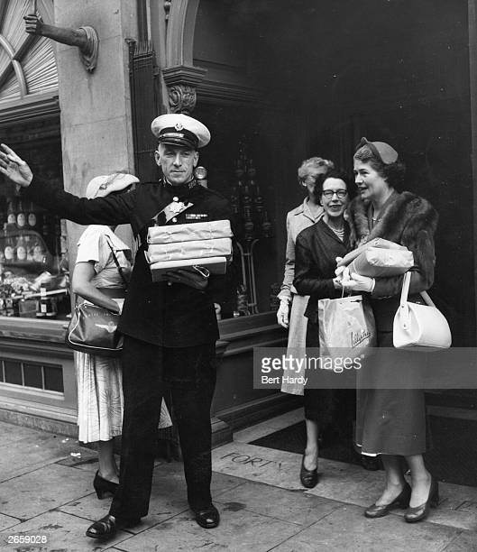 A commissionaire hails a taxi for customers at Fortnum and Mason's store in Piccadilly London