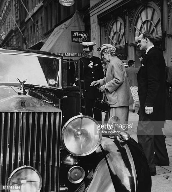 Commissionaire helps a customer in to her Rolls-Royce car outside Fortnum & Mason's store in London.