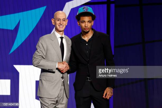 Commissioner Adam Silver and James Bouknight pose for photos after Bouknight was drafted by the Charlotte Hornets during the 2021 NBA Draft at the...