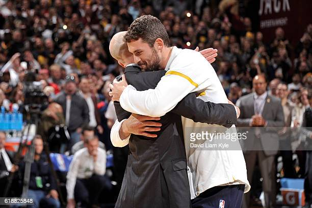 Commissioner Adam Silver hugs Kevin Love of the Cleveland Cavaliers after presenting him with his championship ring before the game against the New...