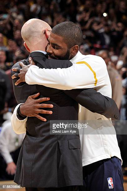 Commissioner Adam Silver hugs Kyrie Irving of the Cleveland Cavaliers after presenting him with his championship ring before the game against the New...