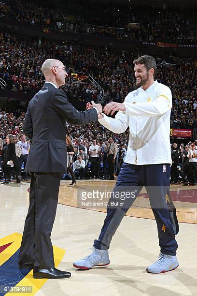 Commissioner Adam Silver shakes hands with Kevin Love of the Cleveland Cavaliers as he gets his championship before the game against the New York...
