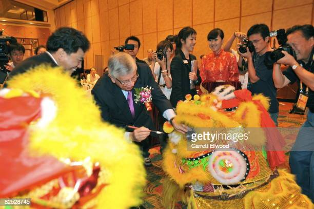 Commissioner David Stern dots the eyes of a dragon durng the Tsingtao Press Conference on August 23 2008 at the Kerry Center in Beijing China NOTE TO...