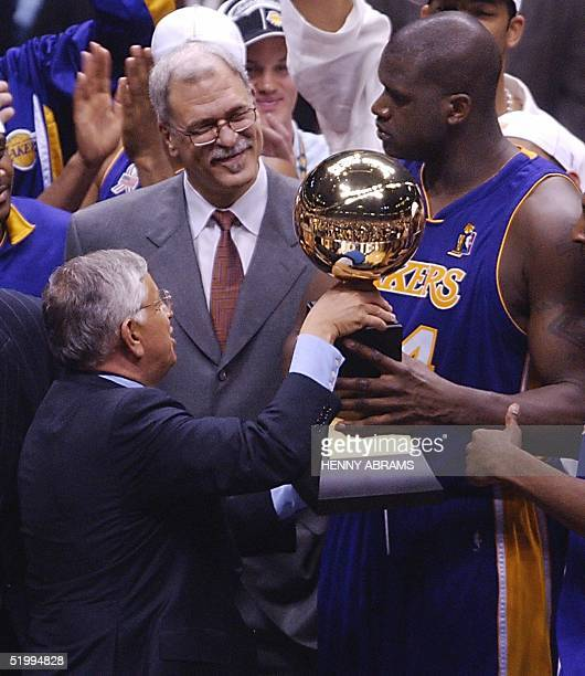 Commissioner David Stern hands Los Angeles Lakers' center Shaquille O'Neal the MVP Trophy before Lakers' head coach Phil Jackson following game four...