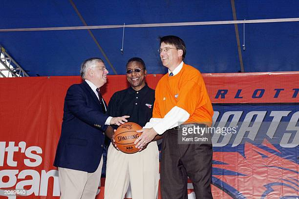 Commissioner David Stern passes the basketball to BET founder Robert Johnson and Charlotte mayor Pat McCrory during a street party for the unveiling...