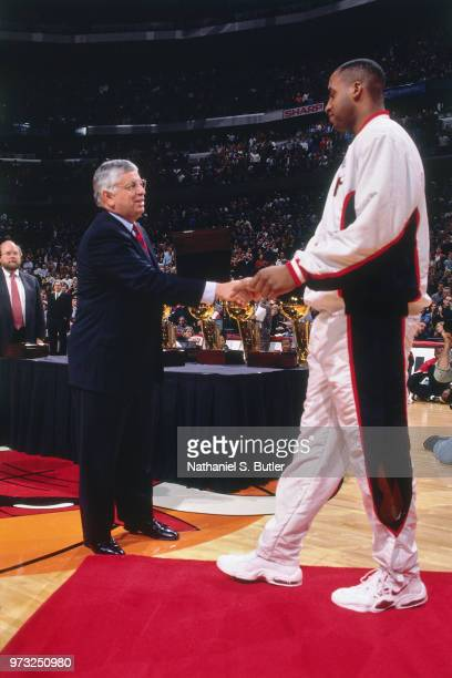 Commissioner David Stern presents Jason Caffey of the Chicago Bulls with a championship ring during a game played on November 1 1997 at the First...