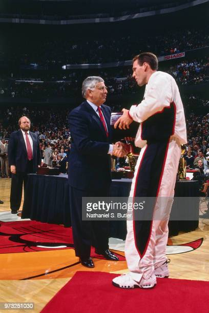 Commissioner David Stern presents Jud Buechler of the Chicago Bulls with a championship ring during a game played on November 1 1997 at the First...