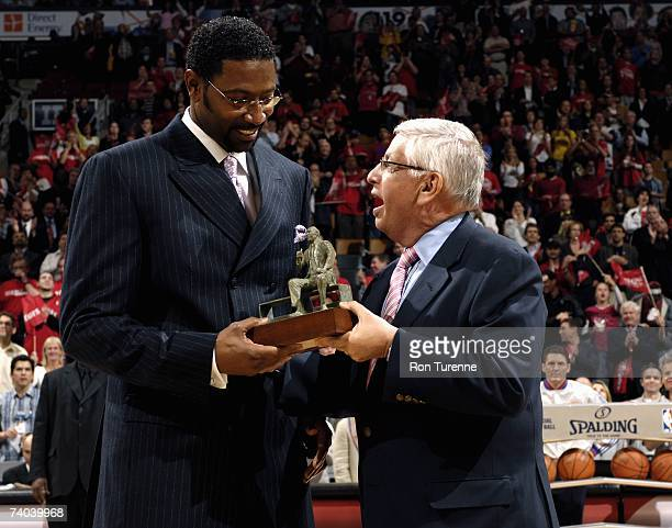 Commissioner David Stern presents Toronto Raptors head coach Sam Mitchell with the Red Auerbach trophy for Coach of the Year before the game against...