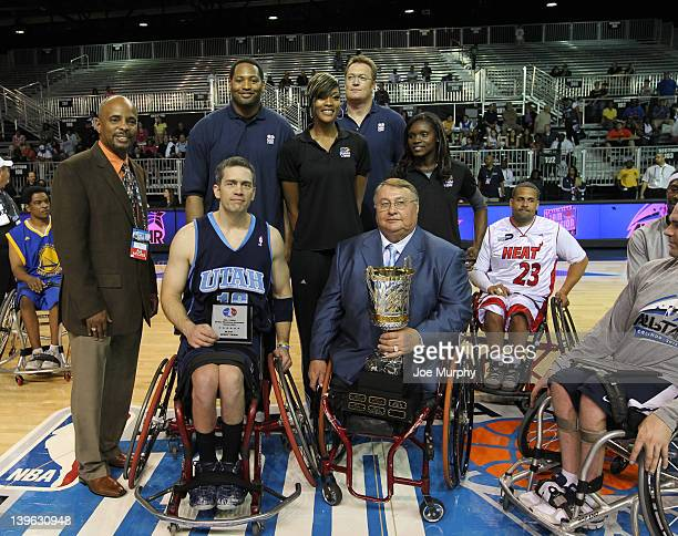 Commissioner Dick Bryant presents a player of the West team with an MVP award with the Honorary Coaches of the West team NBA Legend Robert Horry and...