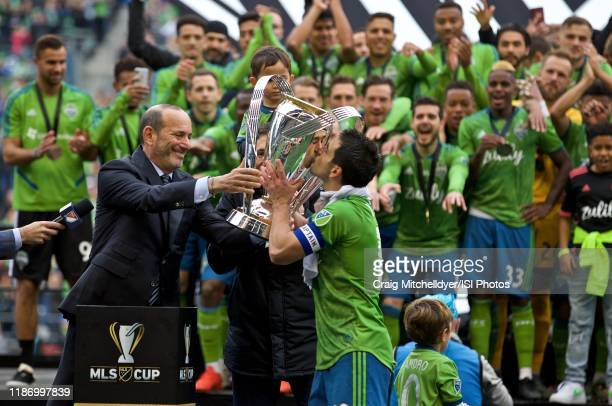 Commissioner Don Garber presents the 2019 MLS Cup to Seattle Sounders midfielder Nicolas Lodeiro during a game between Toronto FC and Seattle...
