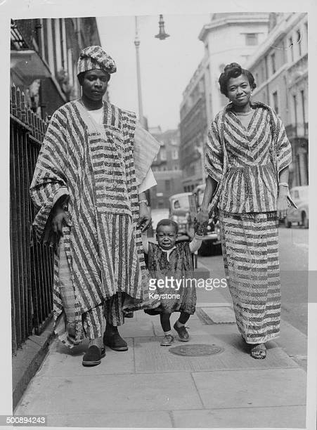 Commissioner for Eastern Nigeria T O C Ojiako with his wife and son Obiora walking through the West End in traditional Nigerian dress London July 5th...