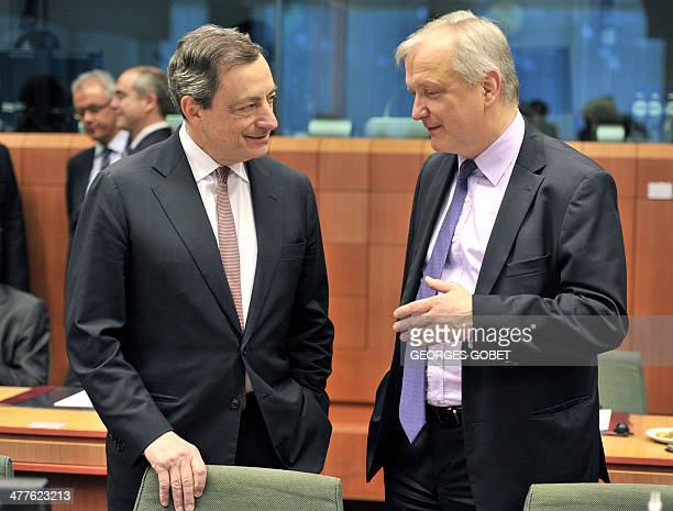 EU Commissioner for Economic and Monetary Affairs Olli Rehn speaks to European Central Bank President Mario Draghi prior to a Eurozone meeting on...