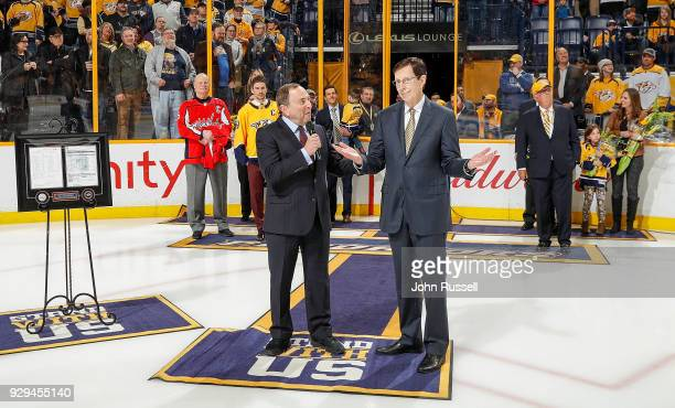 Commissioner Gary Bettman congratulates Nashville Predators GM David Poile on his record breaking 1320 career wins as a GM in the NHL prior to a game...