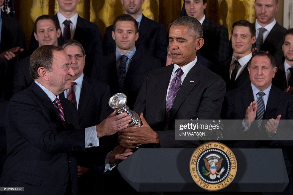 NHL Commissioner Gary Bettman (L) gives US President Barack Obama (R) a replica of the Stanley Cup during an event at the White House in Washington, DC, October 6, 2016, honoring the Pittsburg Penguins 2016 Stanley Cup victory. / AFP / JIM