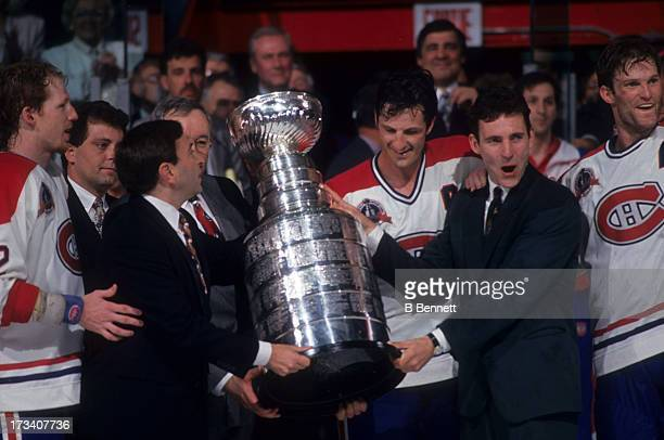 Commissioner Gary Bettman presents the Stanley Cup Trophy to Denis Savard Guy Carbonneau Kirk Muller and Mike Keane of the Montreal Canadiens after...