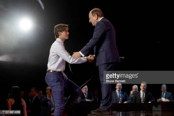 Commissioner Gary Bettman shakes hands with Jack Hughes after being selected first overall by the New Jersey Devils during the first round of the...