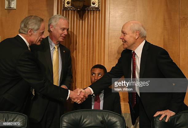 Commissioner John Koskinen shakes hands with Chairman Ron Johnson and Sen. Tom Carper while a Senate staffer sits in the middle, during Senate...