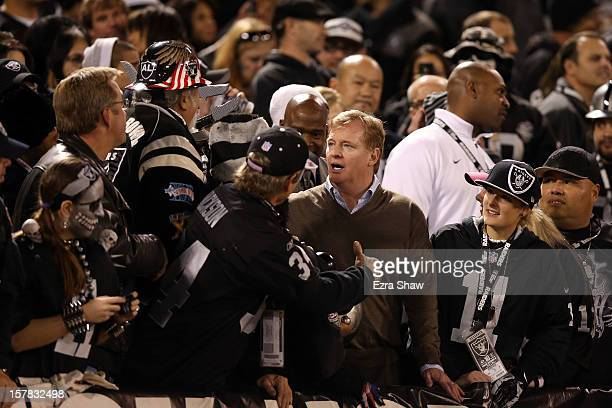 NFL commissioner Roger Goodell stands with fans in the 'Black Hole' as they attend the game between the Oakland Raiders and the Denver Broncos at...