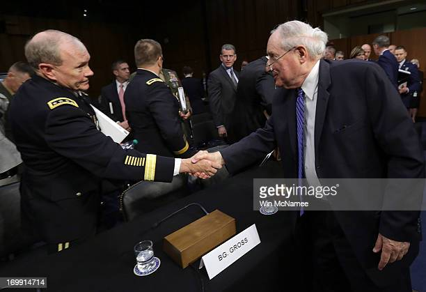 Committee Chairman Sen Carl Levin shakes hands with Chairman of the Joint Chiefs of Staff Gen Martin Dempsey following testimony with US military...