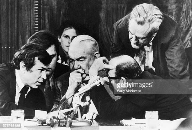Committee Chairman Senator Samuel Ervin confers with his colleagues during the Senate Watergate Hearings in Washington DC The three men surrounding...