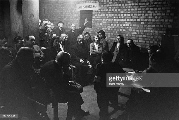 A committee meeting in 'Mickey's Shelter' an improvised airraid shelter in the vaults under the Fruit and Wool Exchange in Brushfield Street...