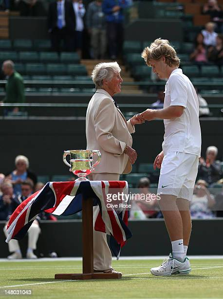 AELTC committee member Ann Jones presents Luke Saville of Australia with his runnersup trophy after his Boys' Singles final match against Filip...