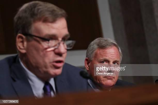 Committee ranking member Sen Mark Warner speaks as committee chairman Sen Richard Burr looks on during a Senate Intelligence Committee hearing...
