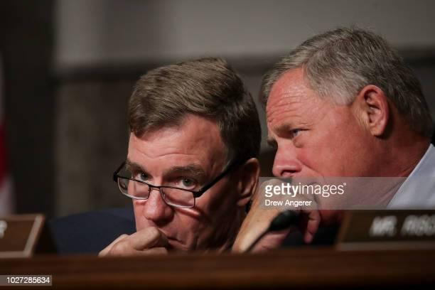 Committee ranking member Sen Mark Warner talks with committee chairman Sen Richard Burr during a Senate Intelligence Committee hearing concerning...