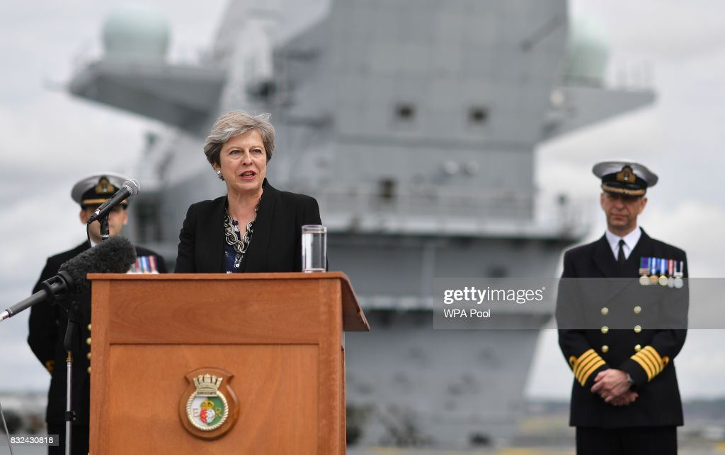 Commodore Jerry Kyd (R), listens as Britain's Prime Minister Theresa May stands on the flight deck and speaks to crew members of the 65,000-tonne British aircraft carrier HMS Queen Elizabeth after it arrived at Portsmouth Naval base, its new home port on August 16, 2017 in Portsmouth, England. The HMS Queen Elizabeth is the lead ship in the new Queen Elizabeth class of supercarriers. Weighing in at 65,000 tonnes she is the largest war ship deployed by the British Royal Navy. She is planned to be in service by 2020 and with a second ship, HMS Prince of Wales, to follow.
